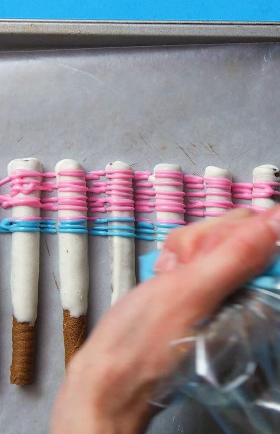 white chocolate wafer sticks being drizzled with colored candy melts